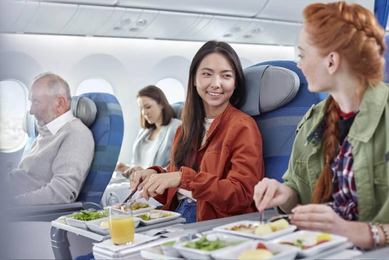 Dos personas sentadas en un avión comiendo
