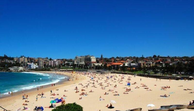 Foto de una playa con mucas personas y edificios de fondo