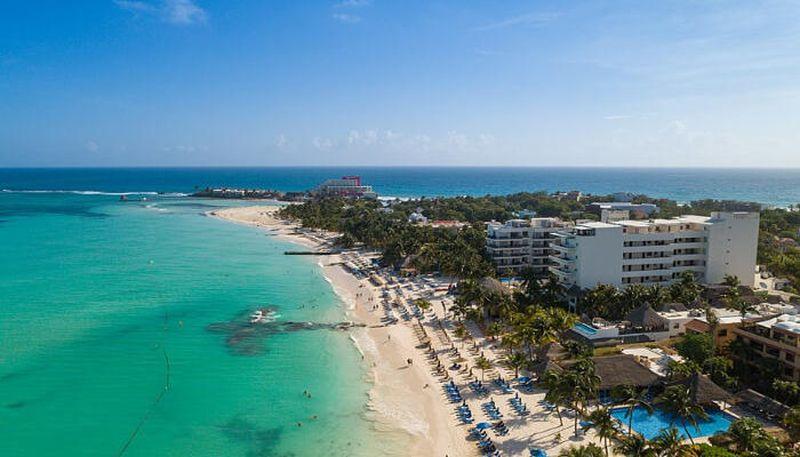 Foto desde el cielo mostrando una playa y edificos de fondo