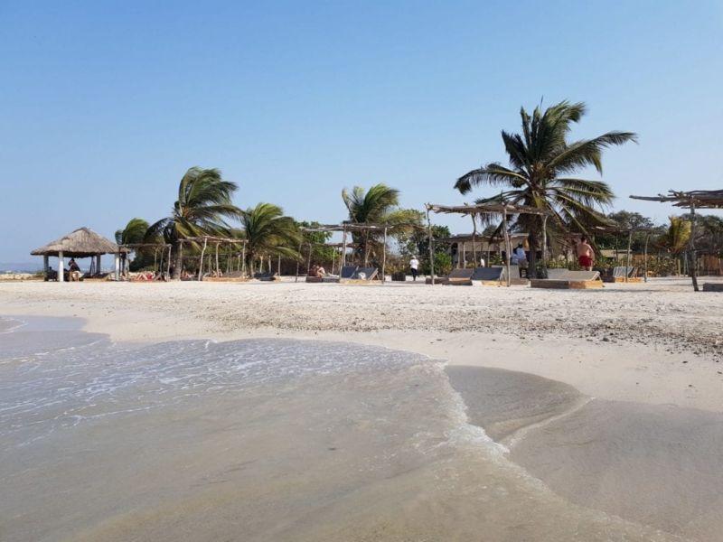 Foto de una playa con un kiosko y con mucho viento